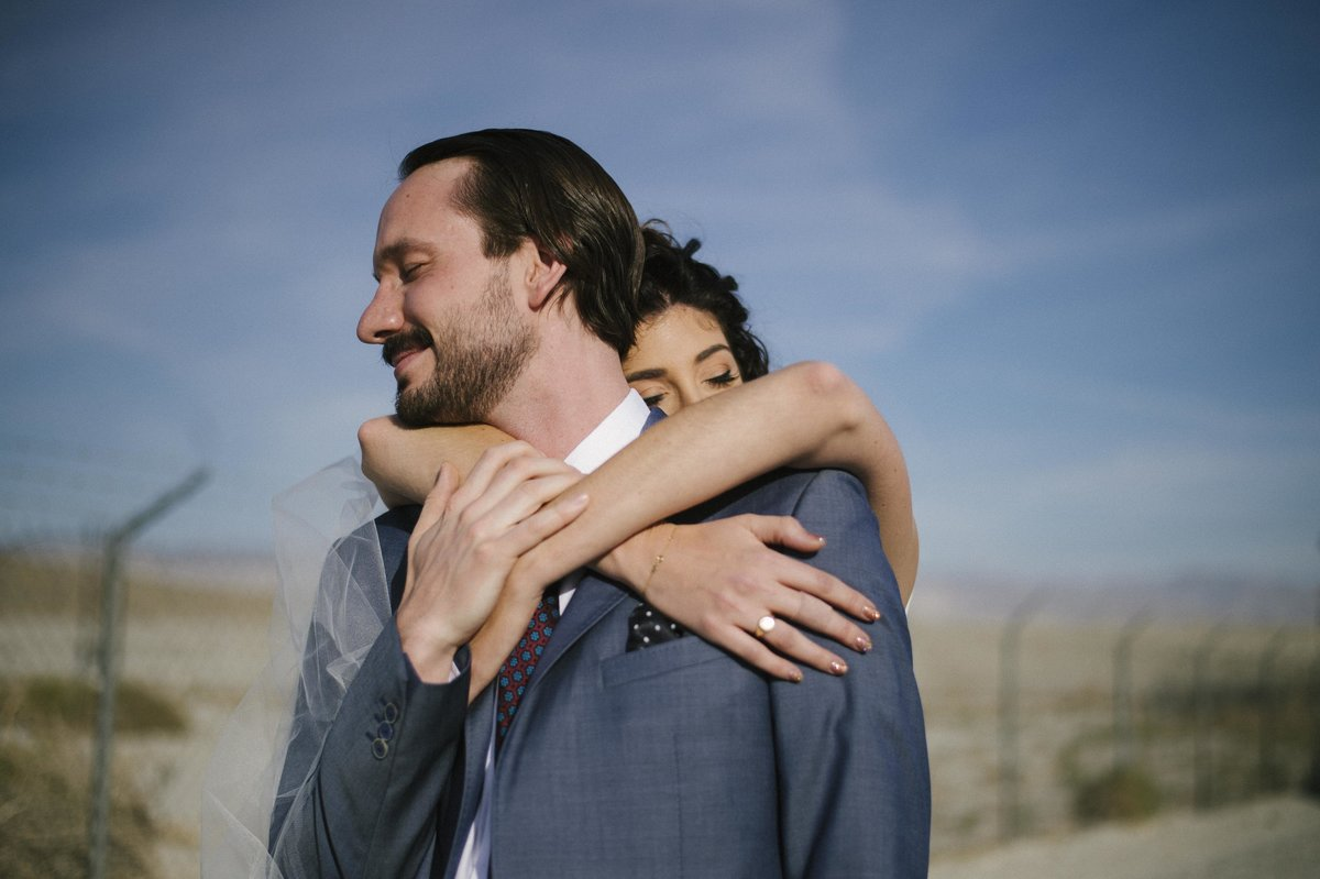 woman embracing man from behind in desert