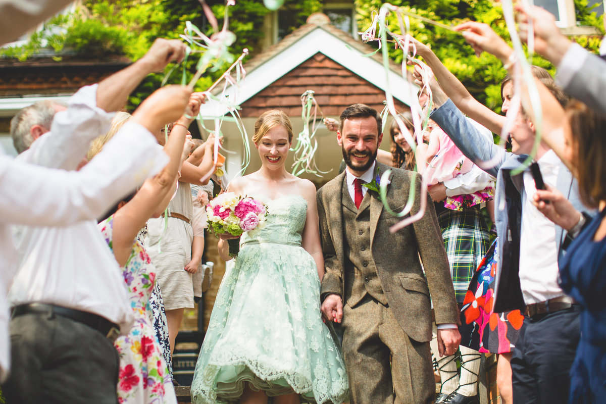 confetti alternative bride in green wedding dress and guests have ribbons on wands