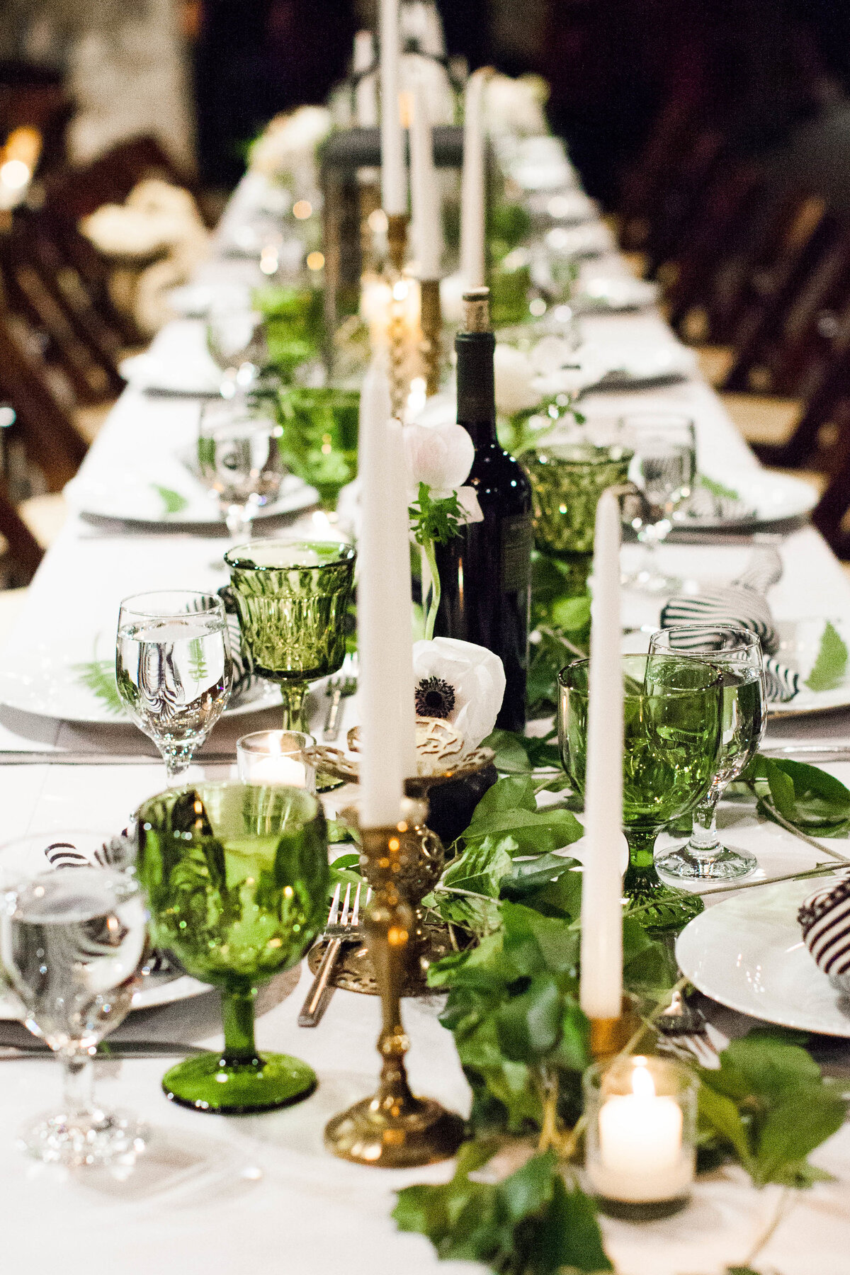 Long head table with greenery and vintage water glasses