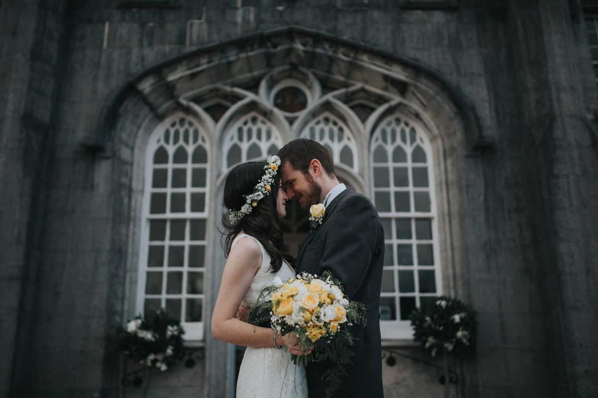 Couple hugging and resting heads together with Leighton Hall, Lancashire as a backdrop - wedding Photography by Jono Symonds