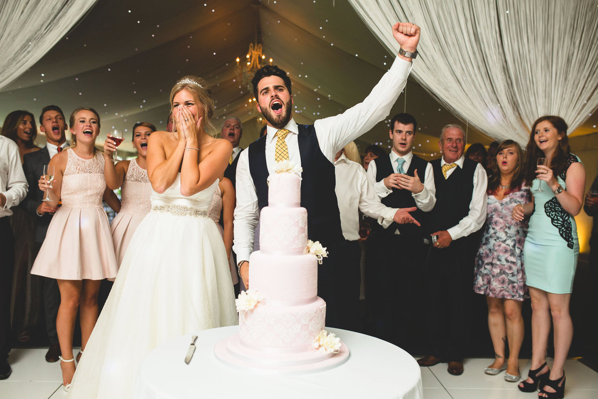 bride and groom cutting the pink wedding cake in a marquee at combermere abbey