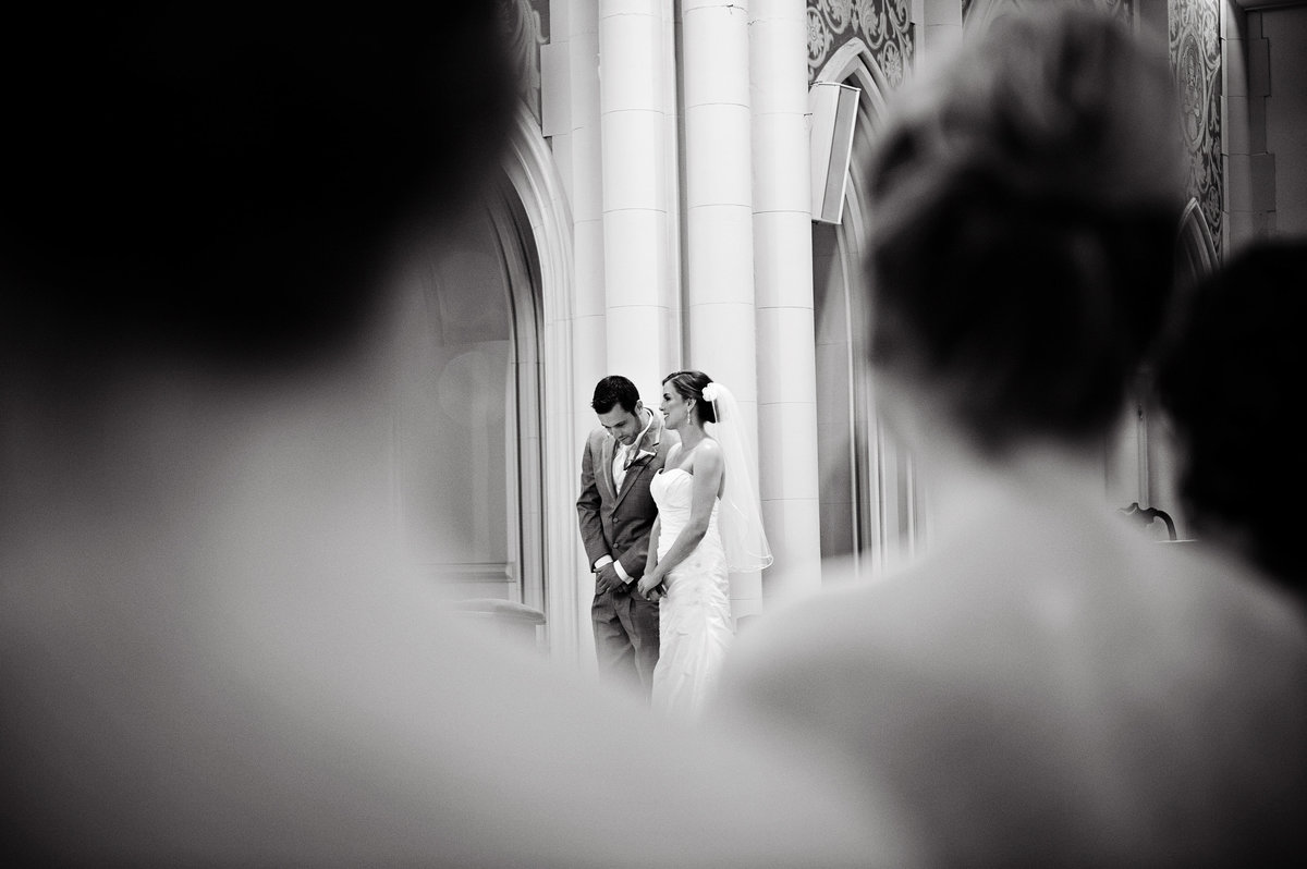 A groom looks over at his bride during their Catholic ceremony in Philadelphia.