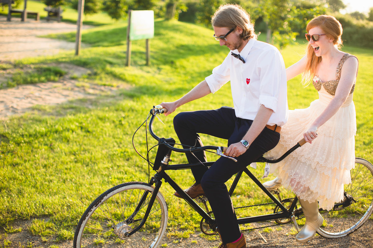 a bride and groom on a tandem bicycle laughing