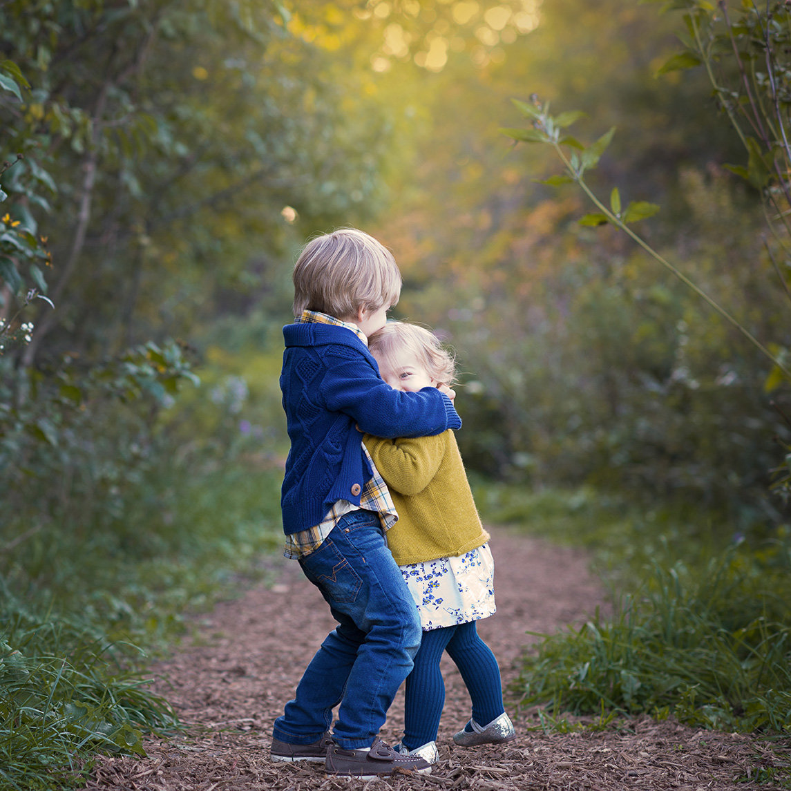 siblings hug in the woods of montrose beach