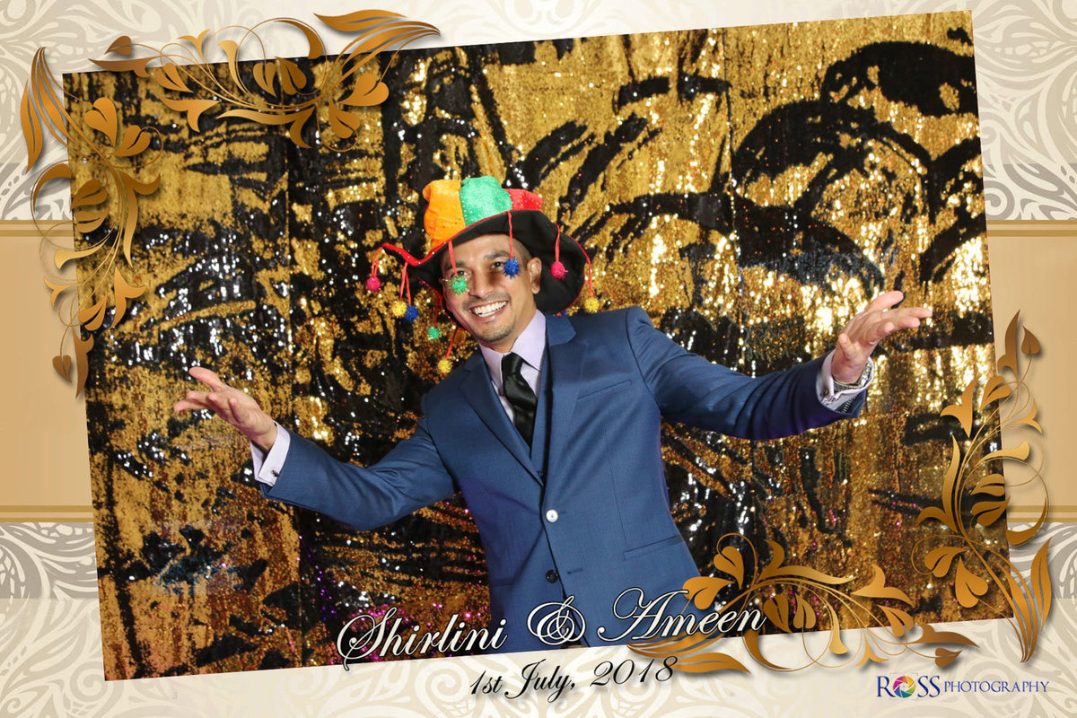 A fun loving man wearing a multicoloured hat with tassels. Photobooth by Ross Photography, Trinidad, W.I..