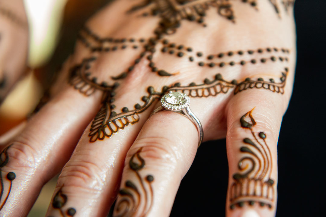 hand of bride decorated with henna designs and displaying her beautiful engagement ring