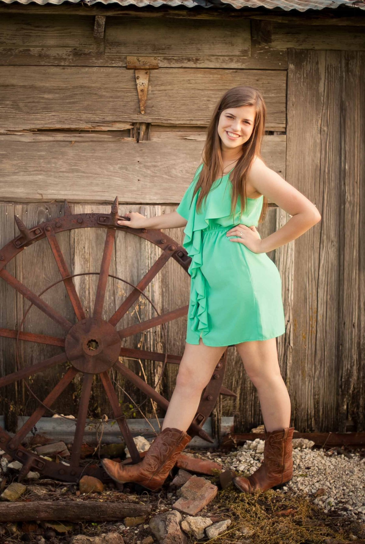 Girl in Cowboy boots at North Texas farm in front of rustic rusted wagon wheel and barn