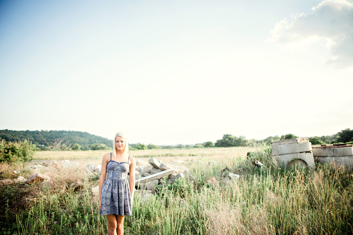 Female standing in a field of tall grass at sunset for her senior pictures by Knoxville Wedding Photographer, Amanda May Photos.
