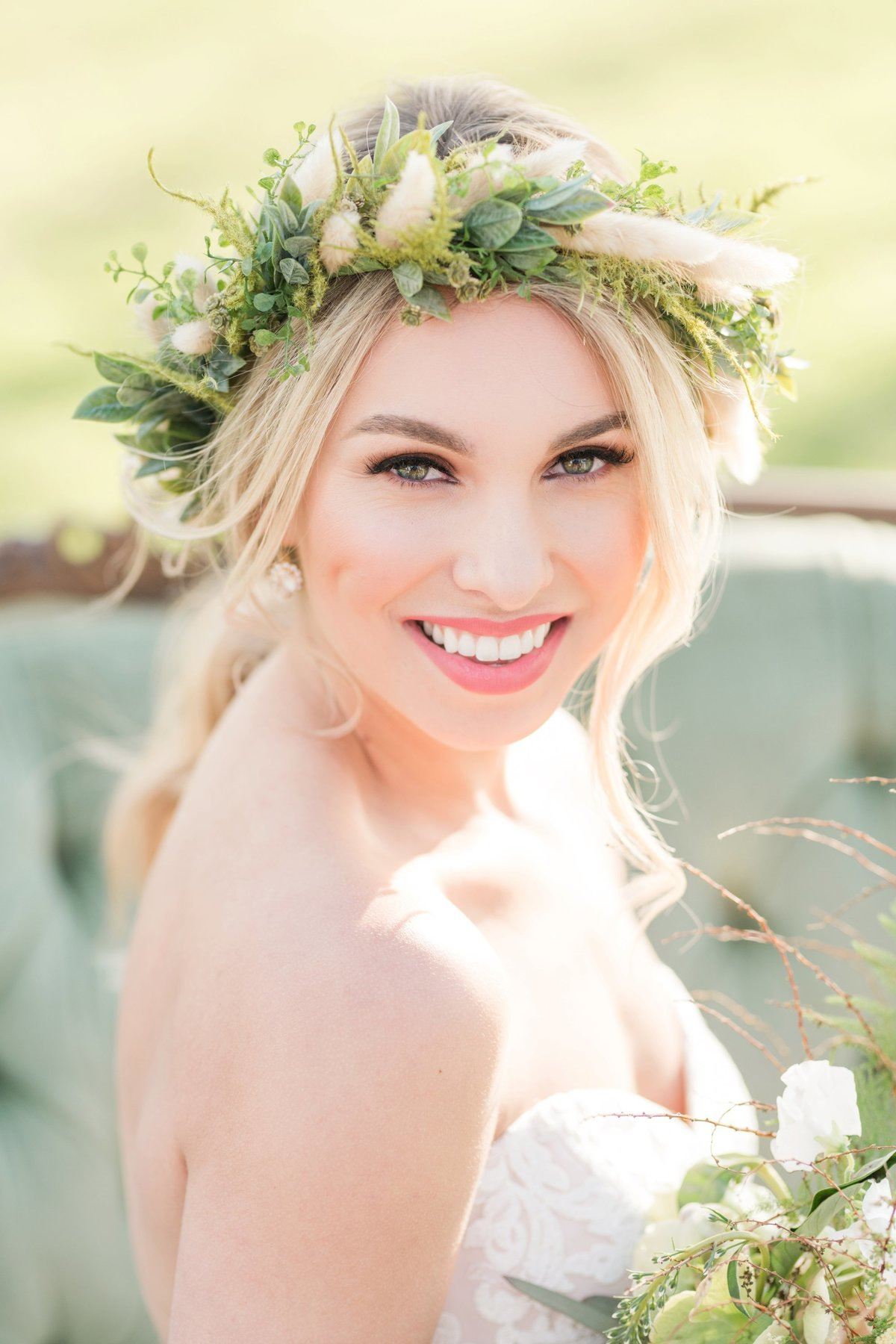 Bride sits on Green couch with fall flower crown for bridal portraits at The White Sparrow Barn