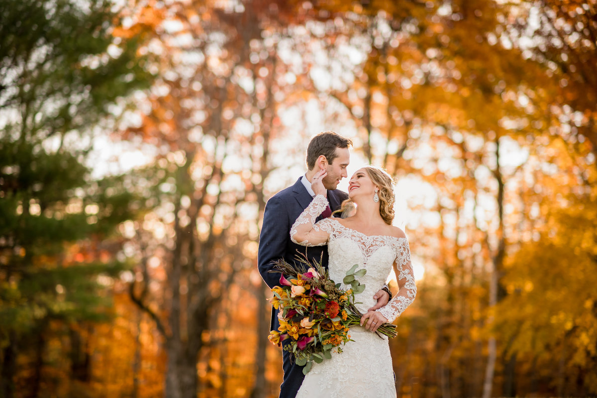 bride and groom looking at each other during fall wedding portraits