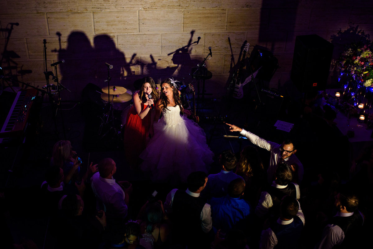 A bride and her maid of honor hop on stage and sing with the band.