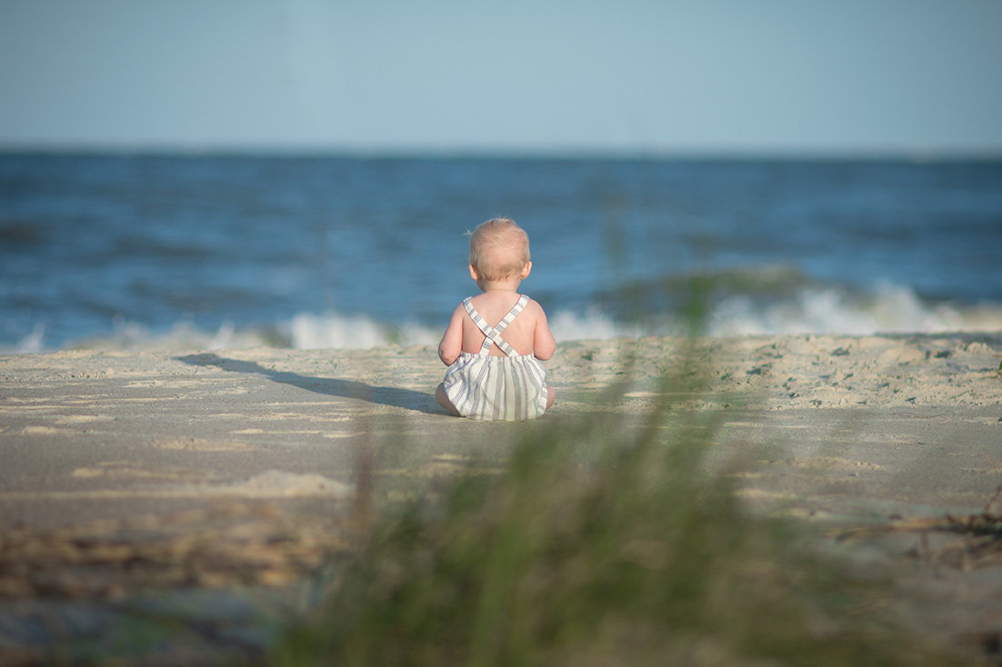 a baby boy watches the waves
