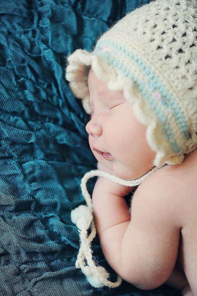 newborn baby wearing her grandmothers knit bonnet