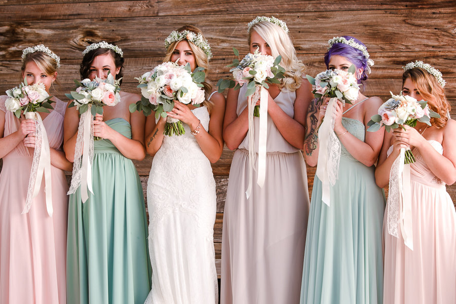 bride and bridesmaids in pastel colors with bouquets playfully covering faces
