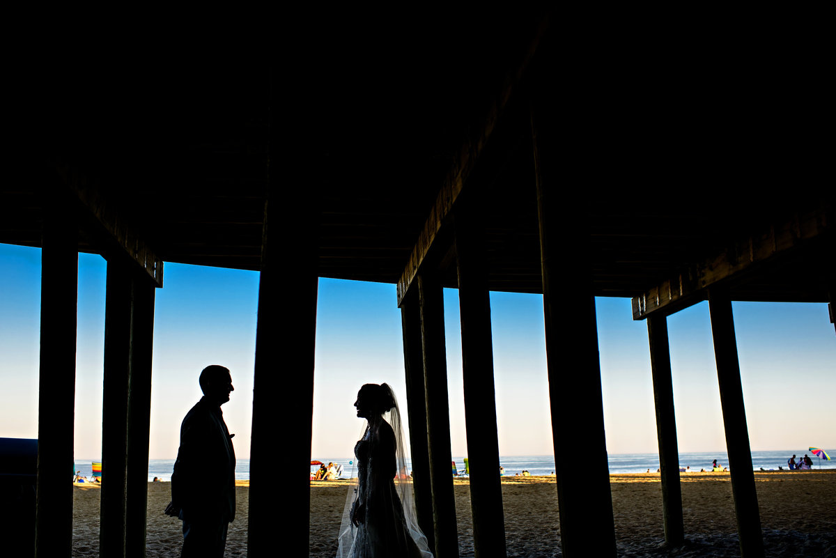 A bride and groom under the pier in long branch, NJ.