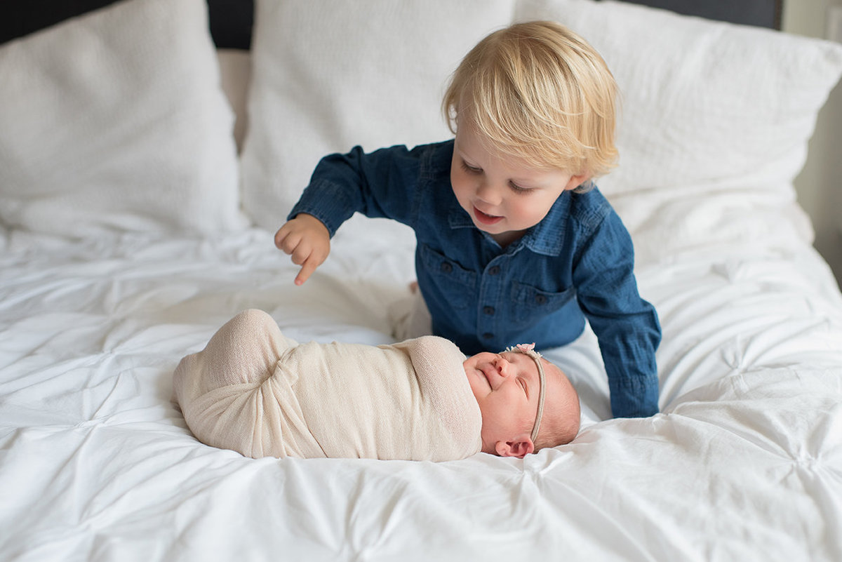 a toddler tickles his new baby sister