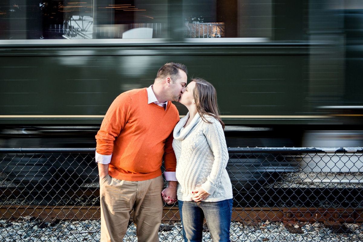 Couple kissing in front of a moving train at Volunteer Landing in Knoxville, TN for their maternity pictures by Knoxville Wedding Photographer, Amanda May Photos.