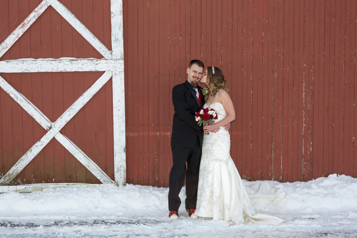 bride and groom in front of a barn in the winter