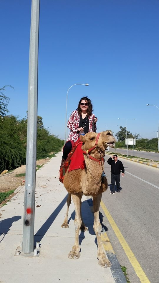 Jill Blue riding a camel in Jordan near the dead sea