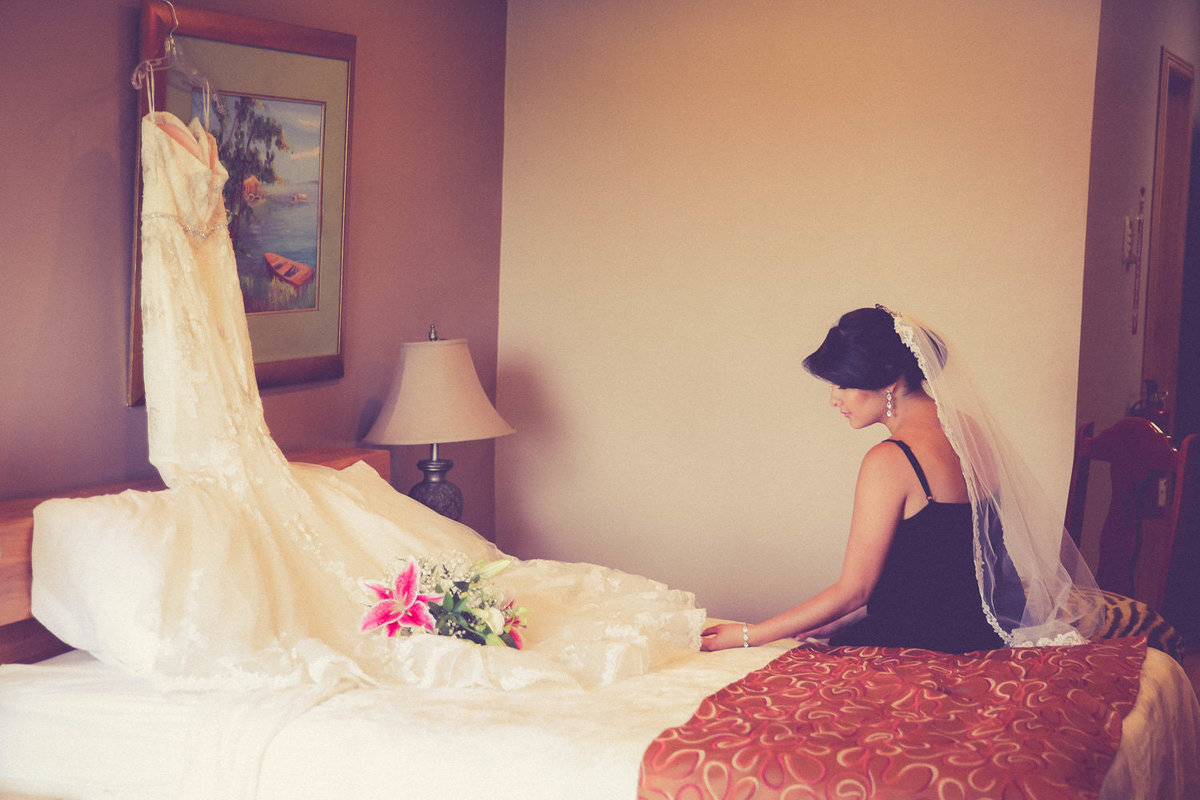 Bride looks at her wedding dress before getting dressed for the wedding. Photo by Ross Photography, Trinidad, W.I..