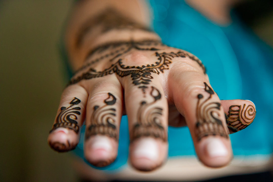 finger tip close up of hand decorated with henna tattoo