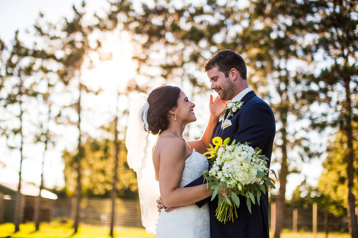 bride toughing grooms face while smiling at williams treefarm in rockton illinois