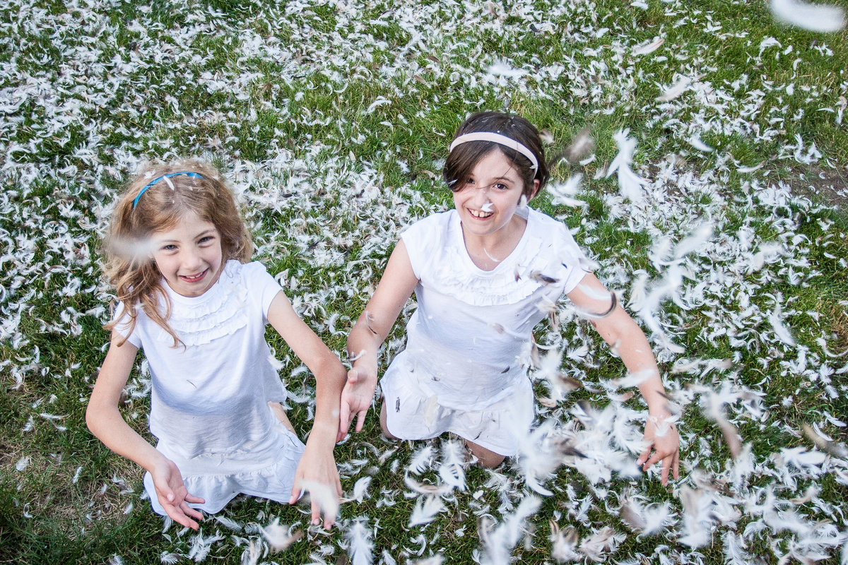 fun best friends tweens kids feather pillow fight by Hudson Valley child photographer in Cornwall NY
