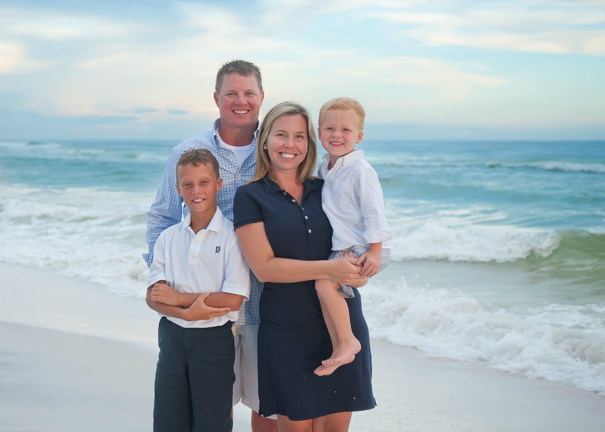 Family with two boys standing on the beach in Watersound 30a