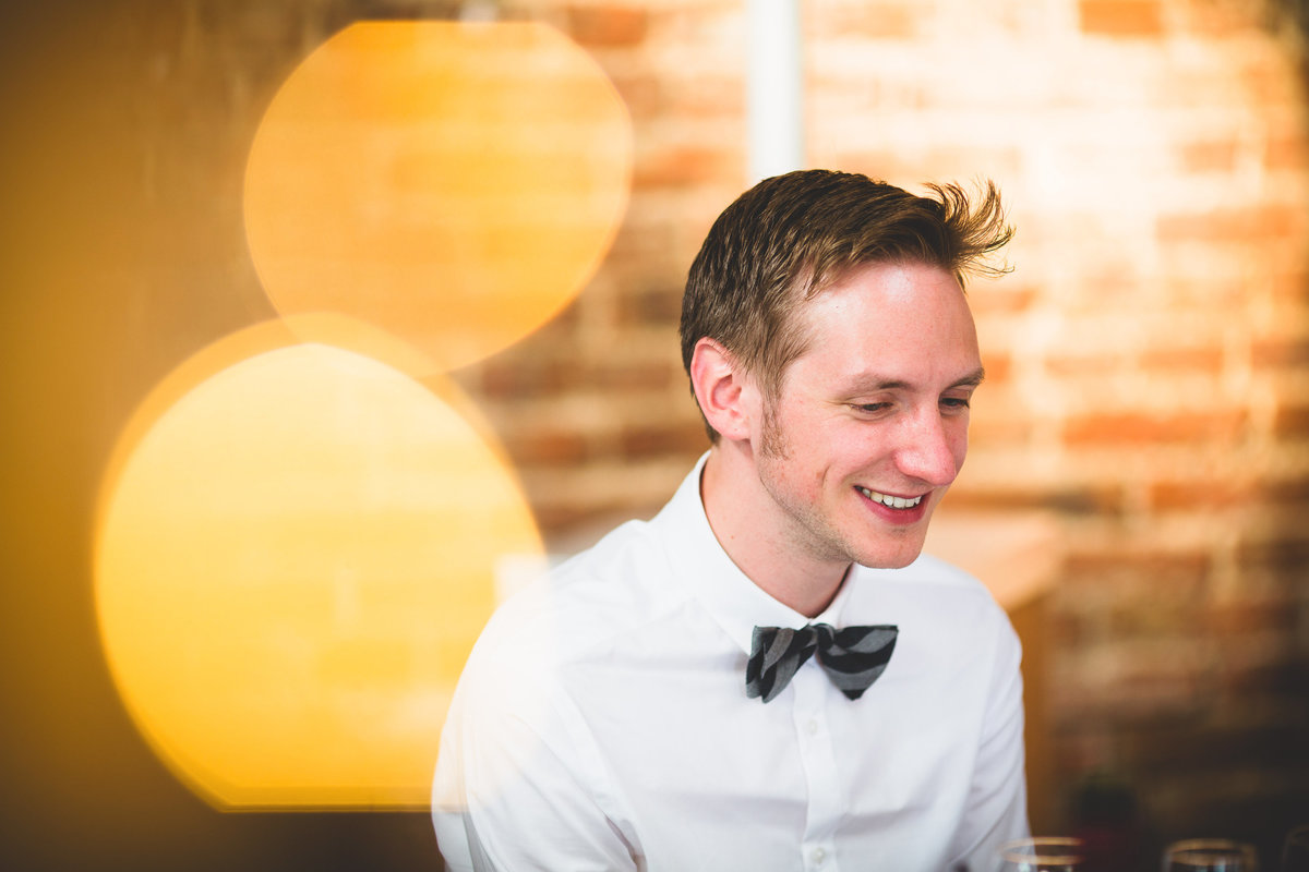 best man laughing in a barn wedding