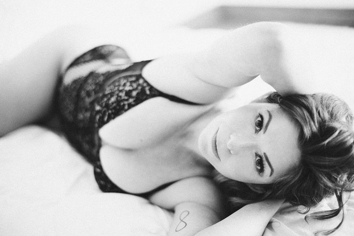 black and white photo of woman laying on bed in victorias secret bodysuit