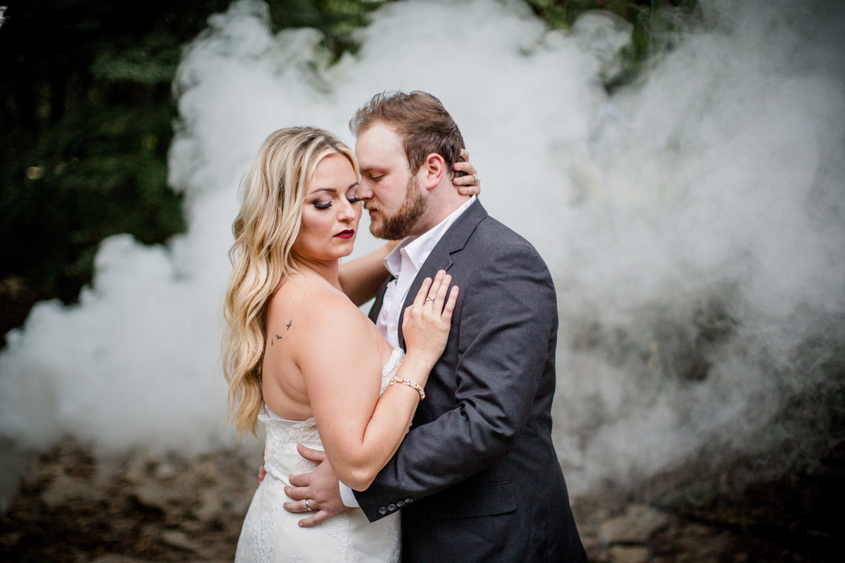 Bride and groom with smoke bombs floating behind them by Knoxville Wedding Photographer, Amanda May Photos.