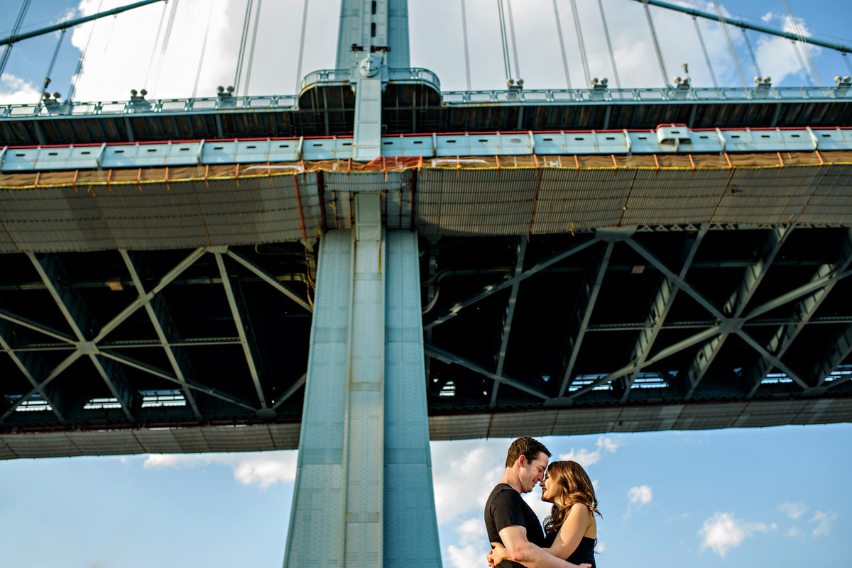 The ben franklin bridge frames a happy couple against the blue sky.
