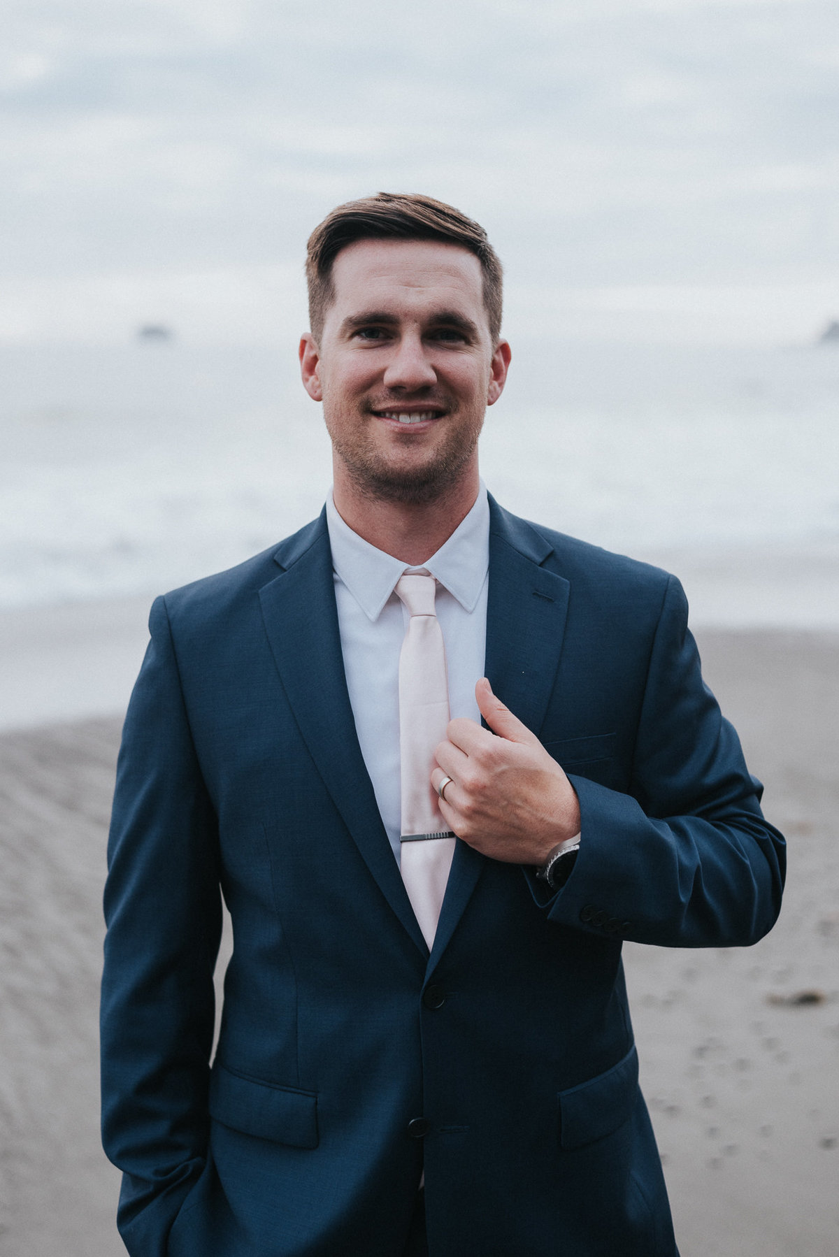 Groom on the moody beaches during his elopement in Forks, Washington