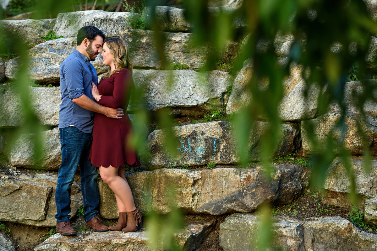 Portrait of a couple on a stone wall at the water works at boathouse row.