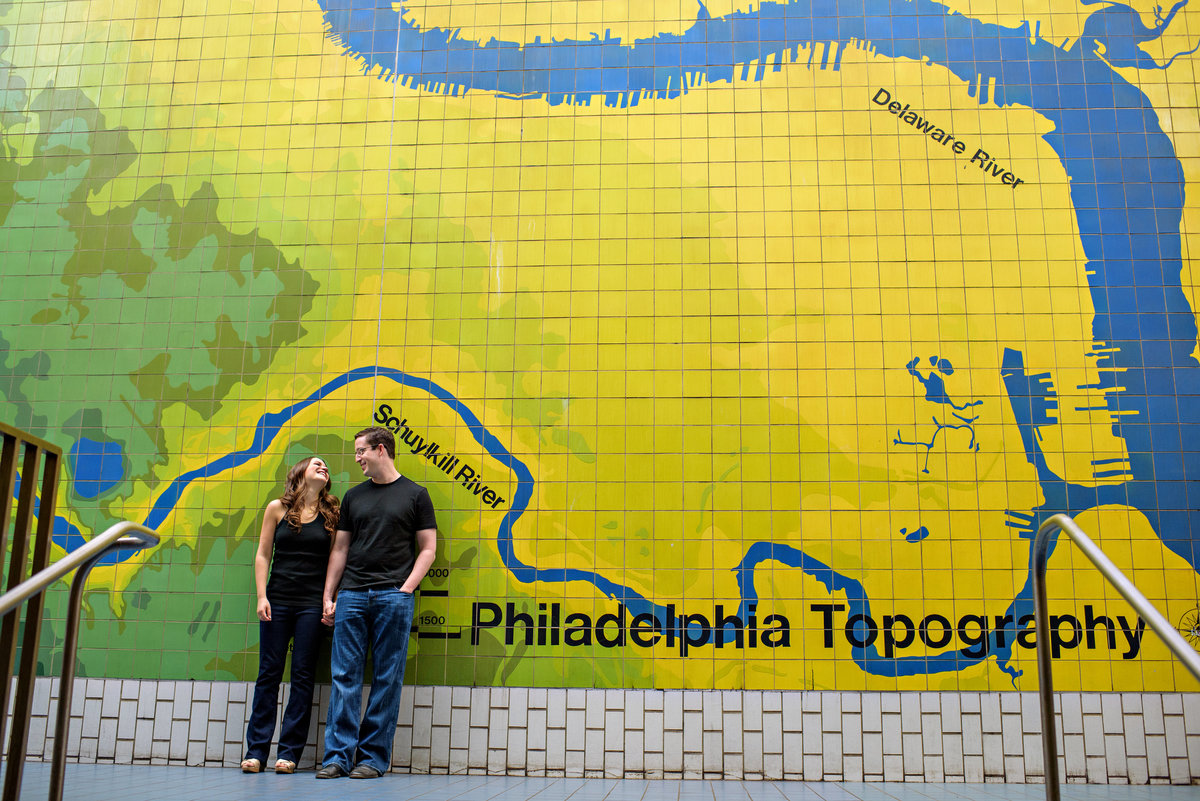 A man and woman lean against a philly mural in the subway.