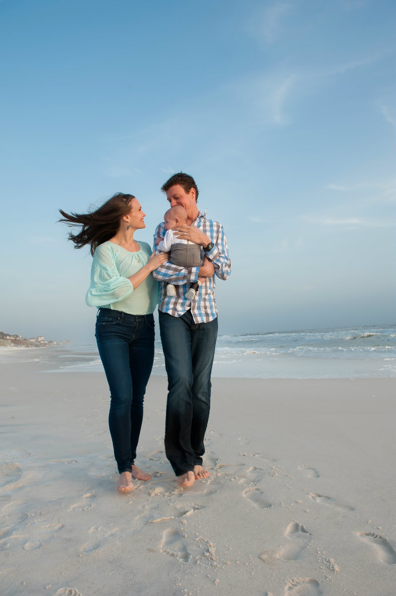 Couple with baby walking on the beach in Seagrove on 30a