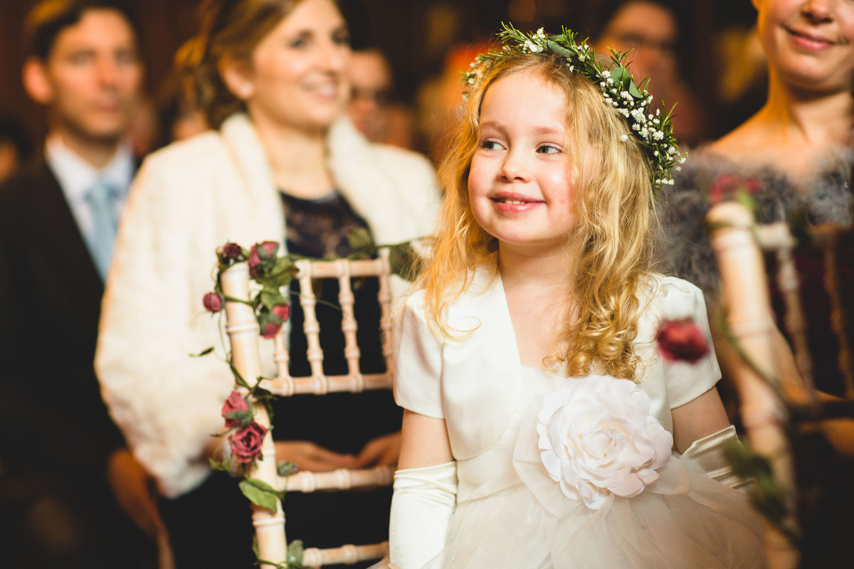a flower girl smiles during the wedding ceremony