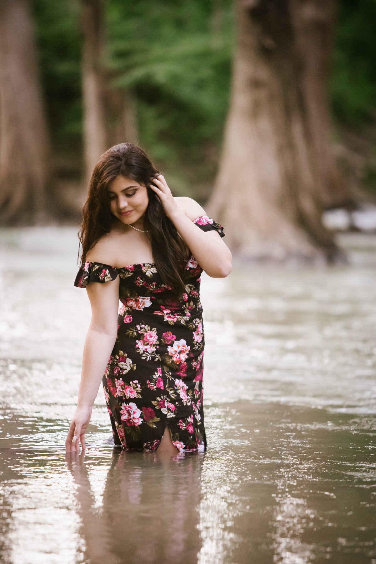 high school senior girl standing in river water in dress by San Antonio senior photographer