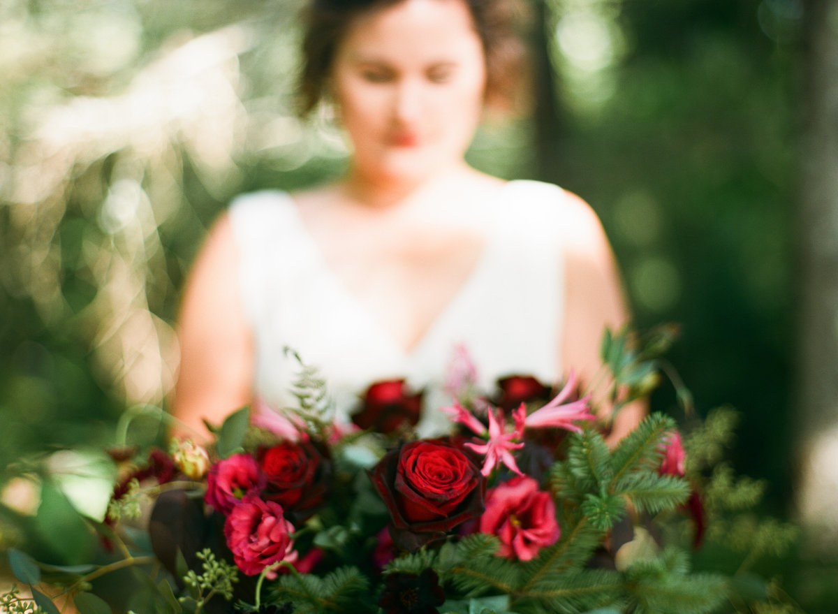 maine camp wedding bride with bouquet in woods