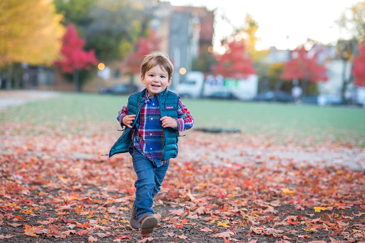 a toddler boy running in the fall leaves
