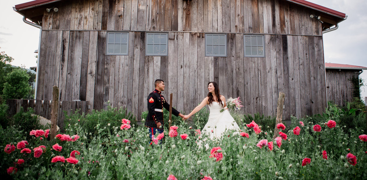 Walking in front of a barn with pink pansies in the foreground at The Barn at Highpoint Farms by Knoxville Wedding Photographer, Amanda May Photos.