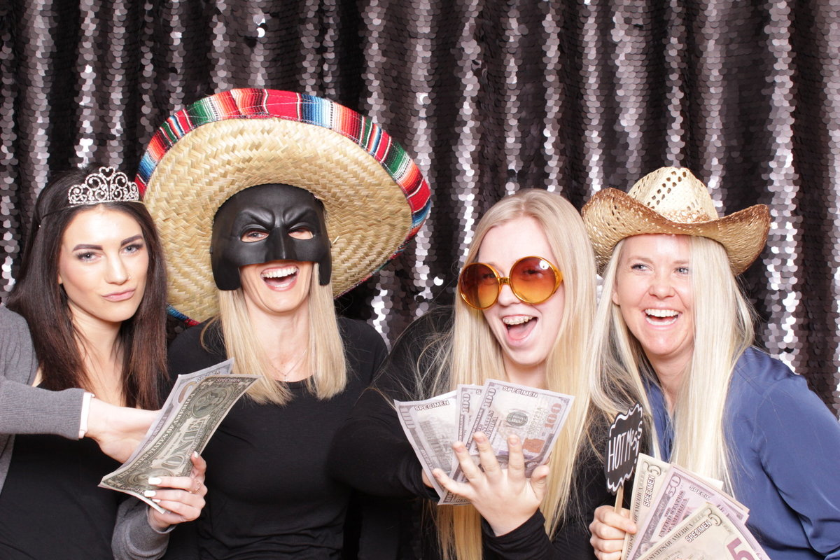 Ladies have fun with props for a photo booth with a black sequin backdrop