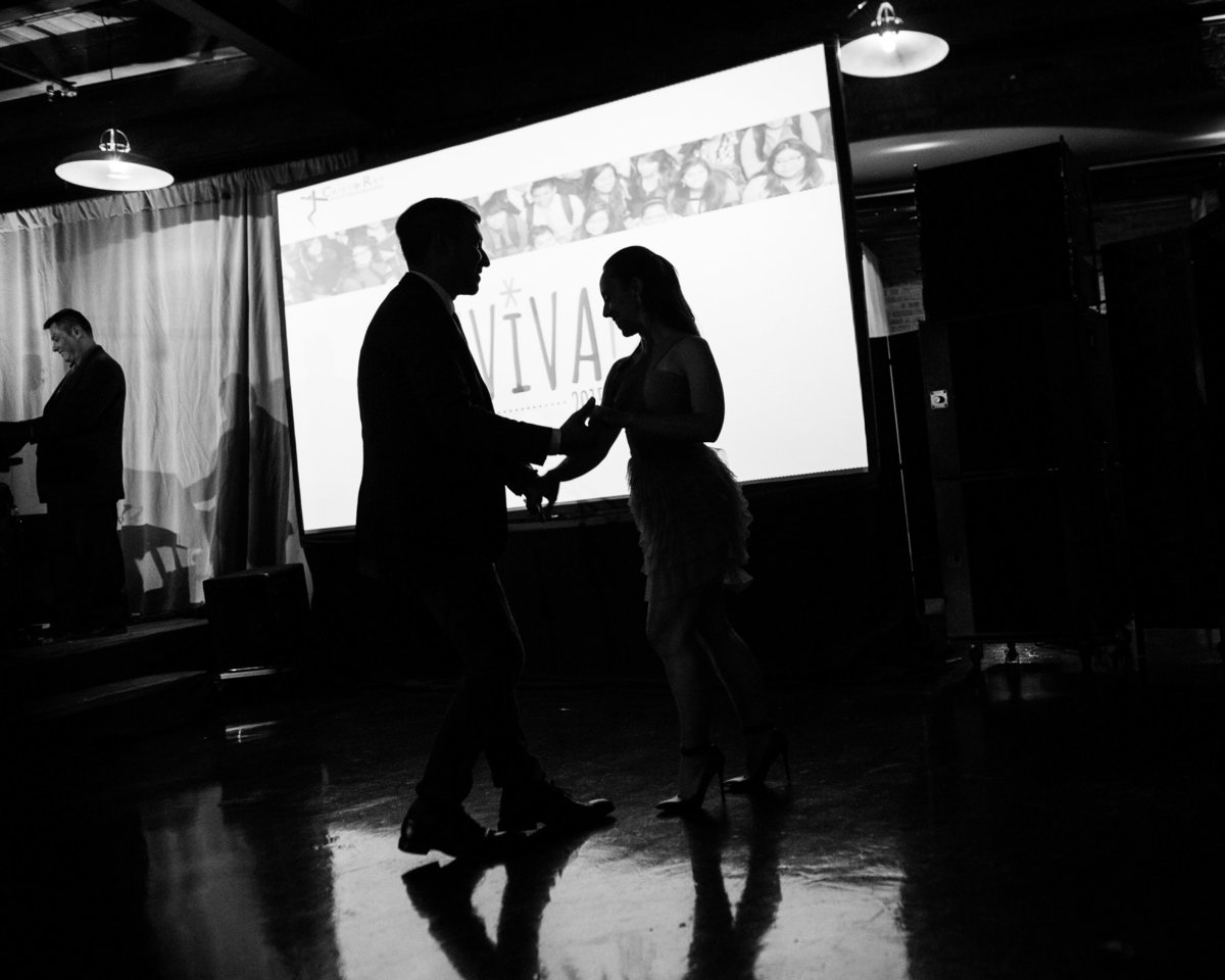 Couple dancing at Chicago event, silhouette, black and white.
