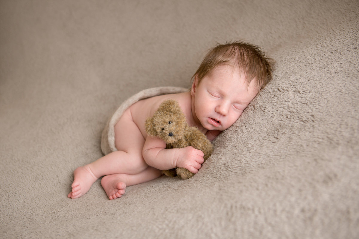 Sleeping newborn baby boy with teddy bear and wrap posed photos on a blanket in Cornwall NY photography studio in the Hudson Valley