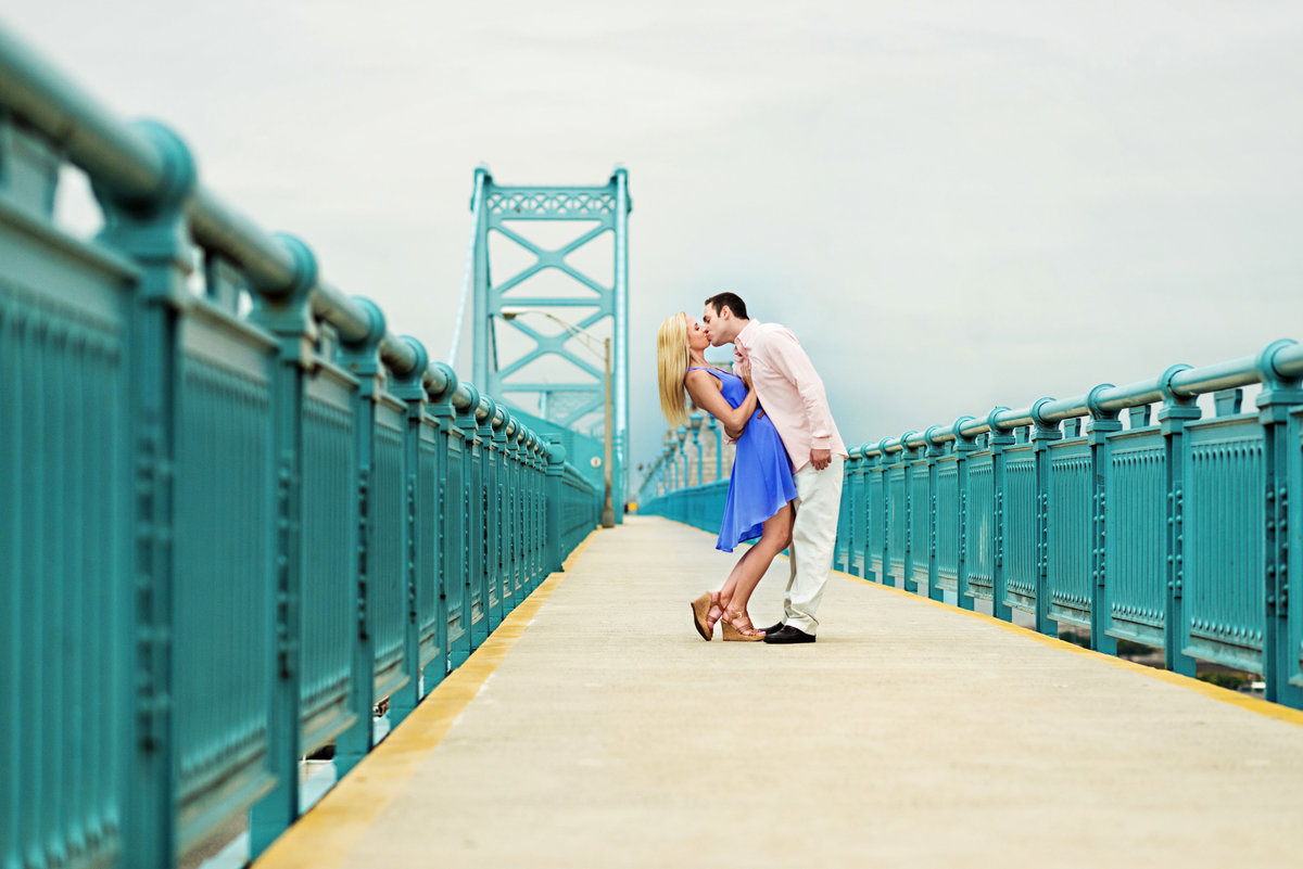 A couple kiss on top of the ben franklin bridge.