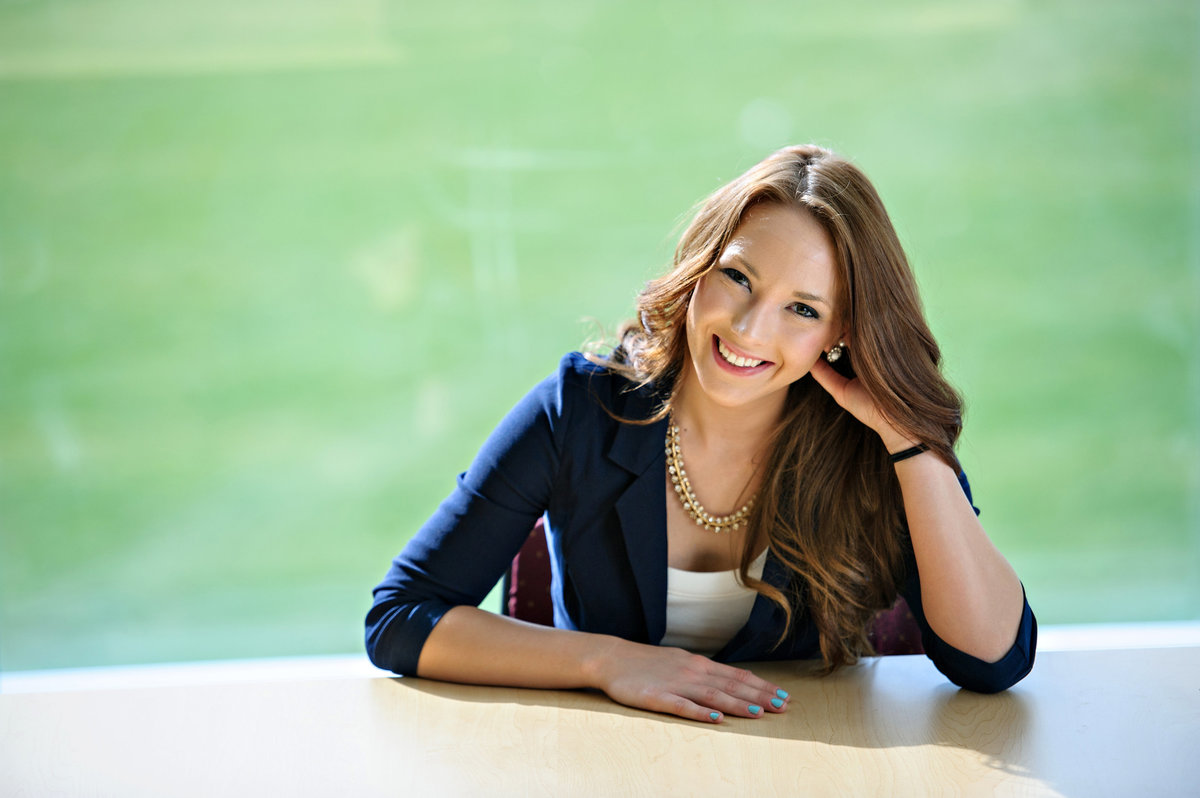A professional woman sits at a desk and smiles with confidence.