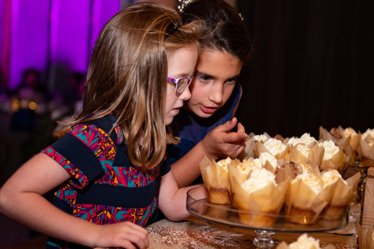 pre teen girls picking cupcakes at reception
