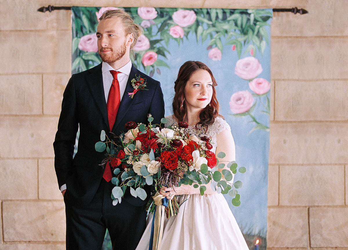 Bride and groom standing in front of Beauty and the Beast inspired floral wedding backdrop By Brittany Branson as featured on Inside Weddings