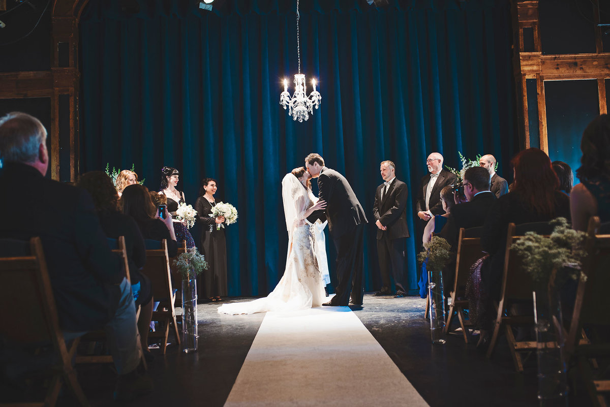 elegant theater wedding, bride and groom first kiss