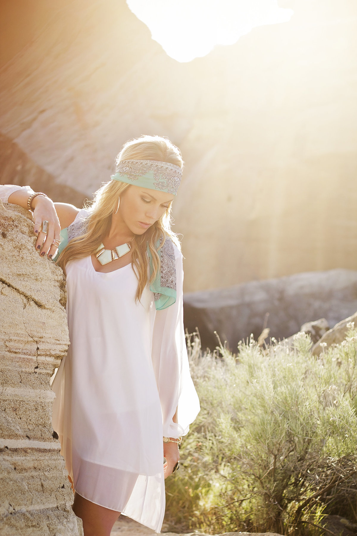 Sun flare portrait of a girl dressed in boho clothes in the Boise foothills